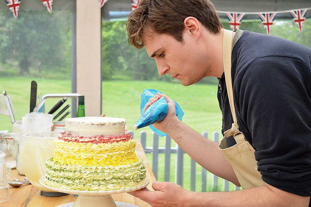 <p>Tom pipes the top of his floral cake on PBS's <i>The Great British Baking Show</i>.<br /><br />(Photo Credit: PBS) </p>
