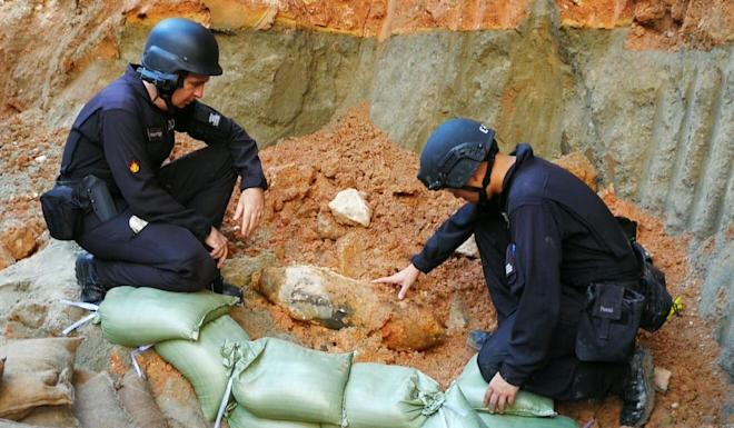 Bomb squad officers study the device found near Kai Tak MTR station. Photo: Handout