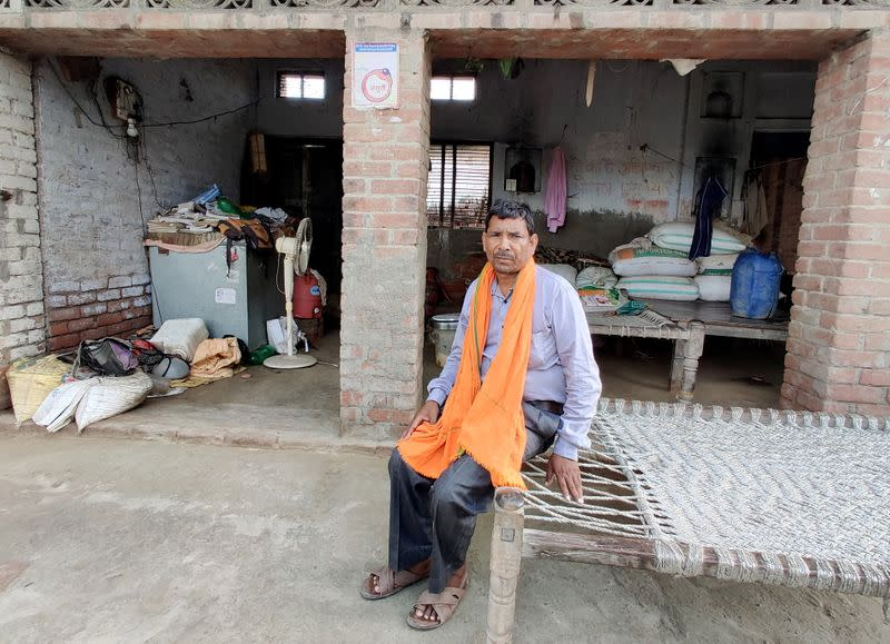 Pasi, a grassroots worker for India's ruling BJP, poses outside his house in Balai village