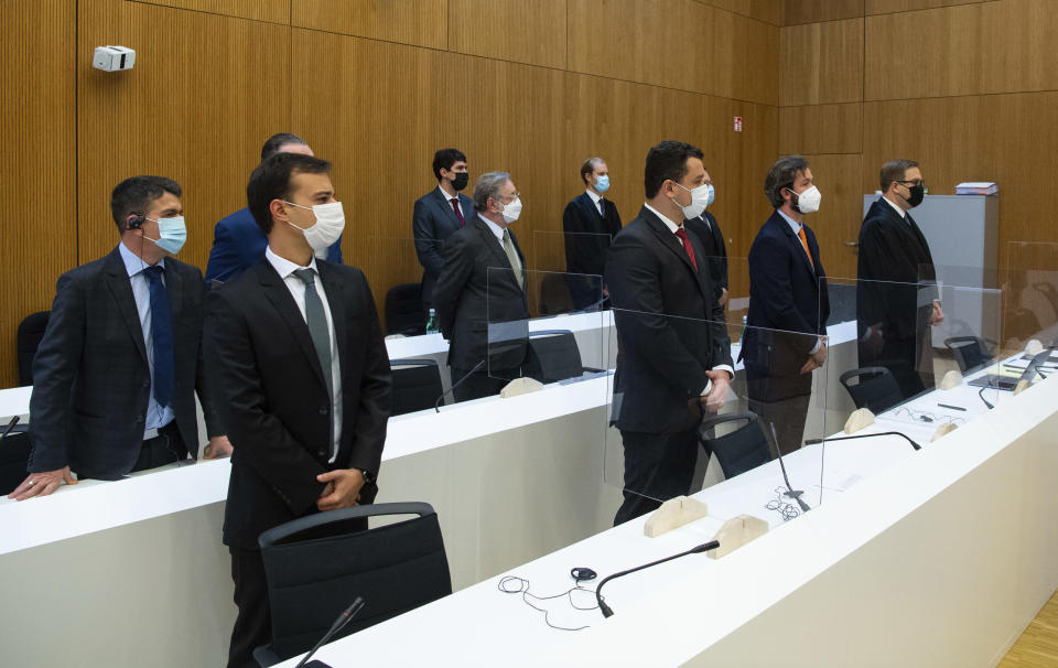 Avimar de Melo Barcelos, back left, mayor of the municipality of Brumadinho, Paulo Richardo Rocha Pinto, husband of a victim, Gustavo Barroso Camara, brother of a victim, lawyer Pedro Martins, and lawyer Jan Erik Spangenberg, left to right, arrive in the courtroom at the Munich Regional Court before the start of the trial in Munich Germany, Tuesday, Sept. 28, 2021. Following the dam disaster in Brumadinho, Brazil, in early 2019, the affected community and the family of one of the 260 fatalities sued TUEV Sued for damages. (Sven Hoppe/dpa via AP)