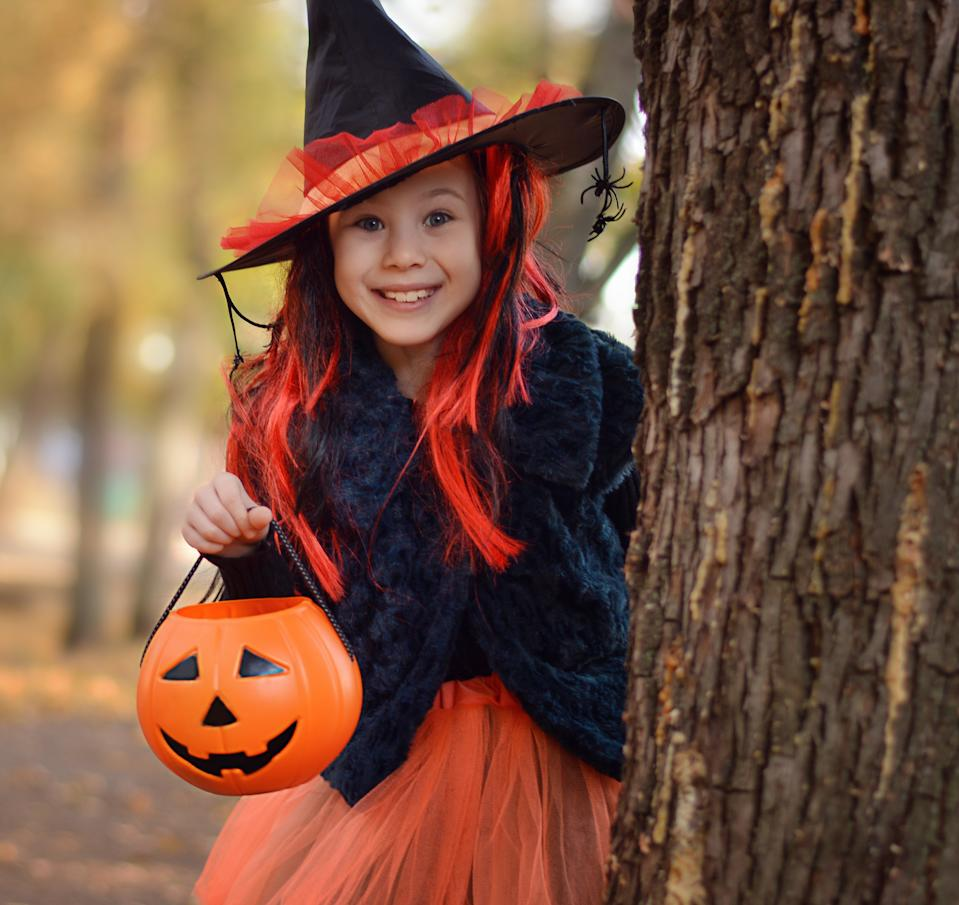 Halloween trick or treat.Happy girl wearing a witch's hat, with a pumpkin handbag, peeps out from behind a tree.. Funny kid in carnival costumes outdoors.