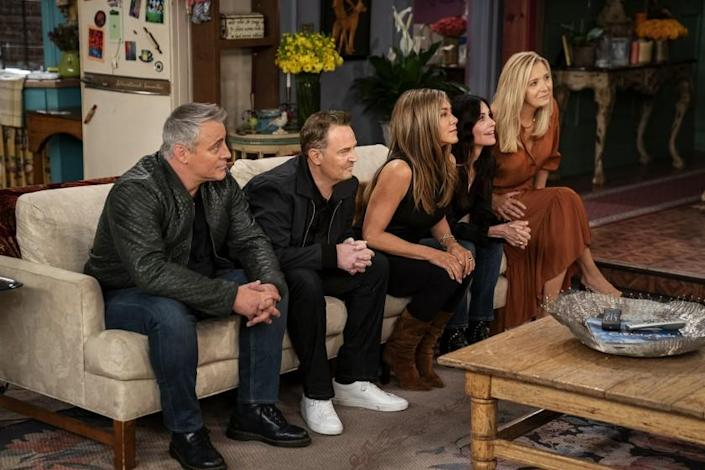 """The cast of """"Friends"""" on a couch in the series' apartment set playing a game"""