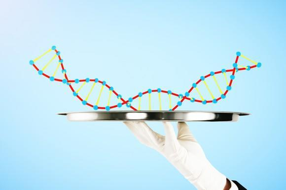 A white-gloved hand holding up a piece of DNA on a silver platter.