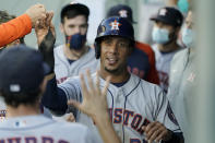 Houston Astros' Michael Brantley is greeted in the dugout after he scored on a single by Taylor Jones during the fourth inning of the team's baseball game against the Seattle Mariners, Saturday, April 17, 2021, in Seattle. (AP Photo/Ted S. Warren)