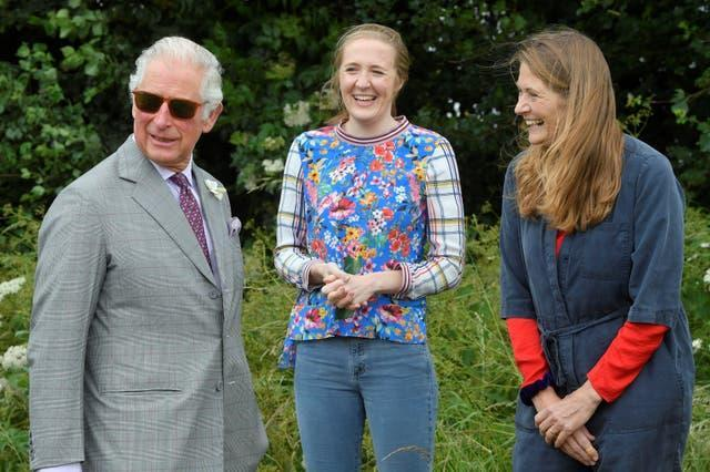 The Prince of Wales speaks with beekeepers Tanya Hawkes (right) and her daughter Esme during his visit to FarmED