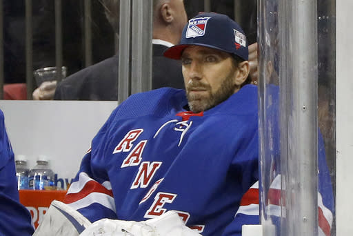 "FILE - Then-New York Rangers goaltender Henrik Lundqvist looks on from the bench during an NHL hockey game against the Buffalo Sabres in New York, in this Friday, Feb. 7, 2020, file photo. Star goalie Henrik Lundqvist will sit out the upcoming NHL season because of a heart condition, announcing the news a little more than two months after joining the Washington Capitals. Lundqvist posted a written statement and a videotaped one on social media Thursday, Dec. 17, 2020, saying it was a ""pretty tough and emotional day."" The 38-year-old from Sweden was bought out by the New York Rangers after 15 seasons and signed a $1.5 million, one-year deal with Washington in October. (AP Photo/Jim McIsaac, File)"