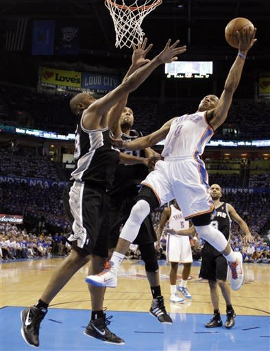Oklahoma City Thunder guard Russell Westbrook (0) shoots as San Antonio Spurs forward Boris Diaw (33), of France ,and center Tim Duncan (21) defend during the first half of Game 4 in the NBA basketball playoffs Western Conference finals, Saturday, June 2, 2012, in Oklahoma City. (AP Photo/Eric Gay)