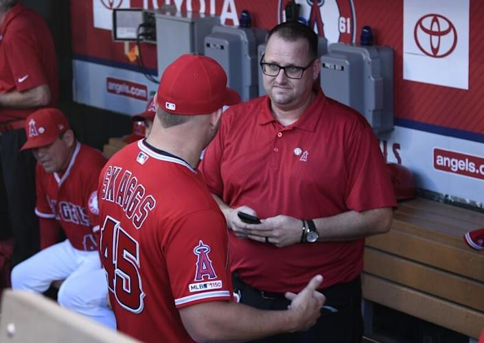 ANAHEIM, CA - JULY 12: Mike Trout of the Los Angeles Angels speaks to Eric Kay in the dugout.