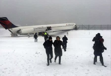 Passengers walk from a Delta jet which skidded off the runway at LaGuardia airport in a photo provided by New York Giants NFL tight end Larry Donnell in New York City March 5, 2015. REUTERS/Larry Donnell