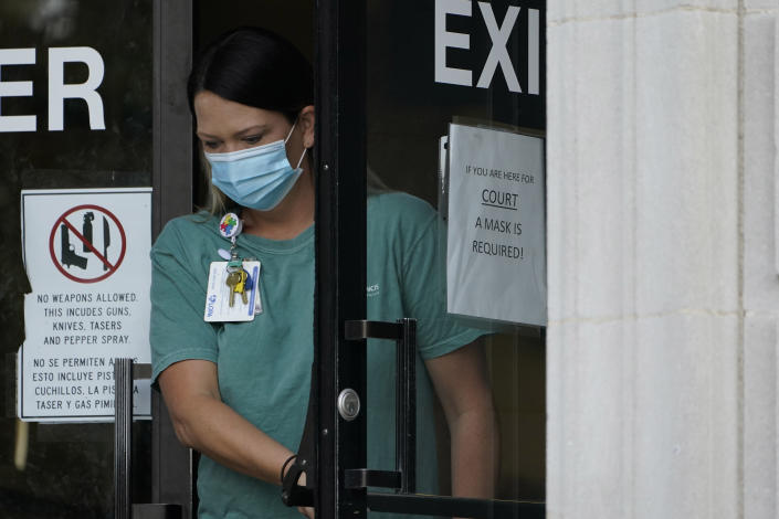 An individual wearing a face mask exits the Ouachita Parish Courthouse in Monroe, La., Thursday, Aug. 5, 2021. Signage at this and other parish offices emphasizes the necessity of wearing a face mask as Louisiana is reinstating a statewide mask mandate for both vaccinated and unvaccinated residents in all indoor locations, including schools and colleges as the state experiences the highest per capita COVID-19 growth in the nation, driven by the Delta variant and one of the country's lowest vaccination rates. (AP Photo/Rogelio V. Solis)