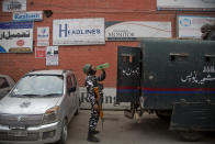 An Indian paramilitary soldier drinks water as he stands guard at the entrance of Press Enclave, which houses several newspaper offices, in Srinagar, Indian-controlled Kashmir, Wednesday, Sept. 8, 2021. Police raided the homes of four journalists on Wednesday, triggering concerns of a further crackdown on press freedom in the disputed region. After the raids in Srinagar, the region's main city, the four journalists were summoned to local police stations where they were questioned. Police did not specify the reason for the raids. (AP Photo/Mukhtar Khan)