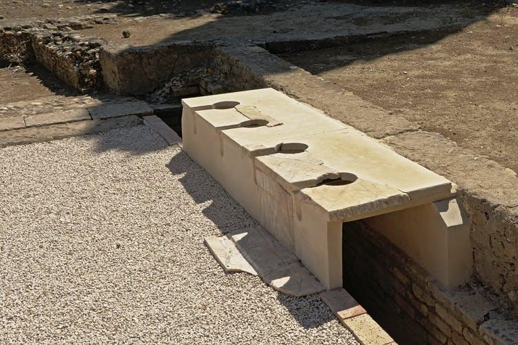 A stone sill overhanging a straight ditch with holes at regular intervals.
