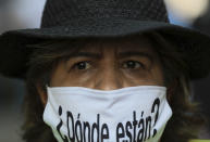 """A person wears a mask with the Spanish question: """"Where are they?"""" during a march in remembrance of those who have disappeared, on Mother's Day in Mexico City, Monday, May 10, 2021. (AP Photo/Fernando Llano)"""