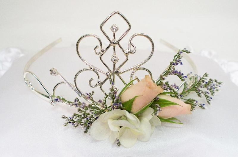 This product image released by Gillespie Florists, Inc. shows a tiara made of rhinestones, two peach sweetheart roses, a few small florets of white hydrangea bloom and limonium.  (AP Photo/Gillespie Florists, Inc.)