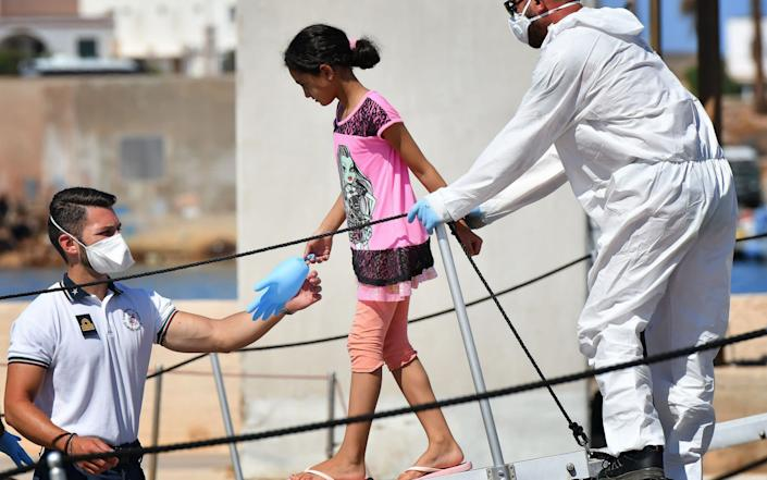 A migrant girl disembarks from an Italian coast guard vessel in Lampedusa - AFP