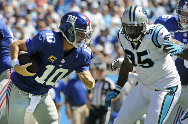 New York Giants quarterback Eli Manning (10) tries to escape the tackle of Carolina Panthers defensive end Charles Johnson (95) during the first half of an NFL football game in Charlotte, N.C., Sunday, Sept. 22, 2013. Manning was sacked on the play. (AP Photo/Mike McCarn)