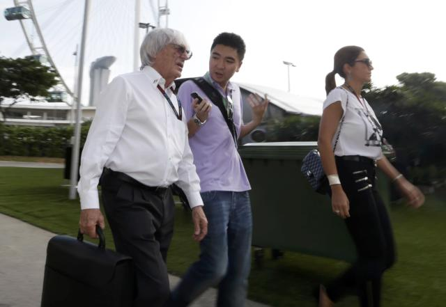 Formula One Chief Executive Bernie Ecclestone (L) and his wife Fabiana Flosi (R) walk with an unidentified man ahead of the third practice session of the Singapore F1 Grand Prix at the Marina Bay street circuit in Singapore September 21, 2013. REUTERS/Pablo Sanchez (SINGAPORE - Tags: SPORT MOTORSPORT F1)