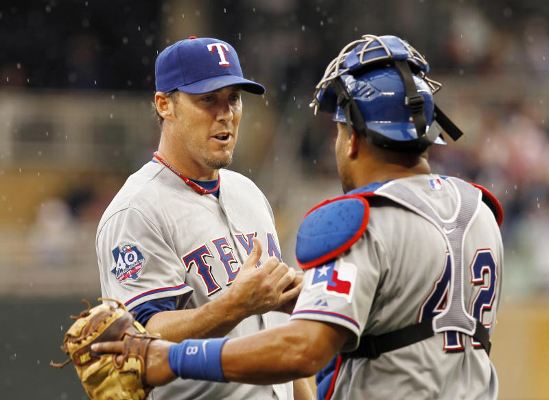 Texas Rangers pitcher Joe Nathan, left, celebrates with catcher Yorvit Torrealba after getting the save and defeating the Minnesota Twins 4-3 in a baseball game on Sunday, April 15, 2012, in Minneapolis. (AP Photo/Genevieve Ross)