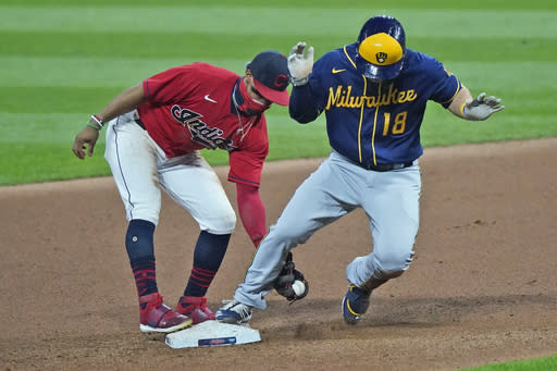 Milwaukee Brewers' Keston Hiura, right, is safe at second base on a one-run double in the seventh inning as Cleveland Indians' Francisco Lindor, left, is late on the tag in the seventh in a baseball game, Friday, Sept. 4, 2020, in Cleveland. (AP Photo/Tony Dejak)