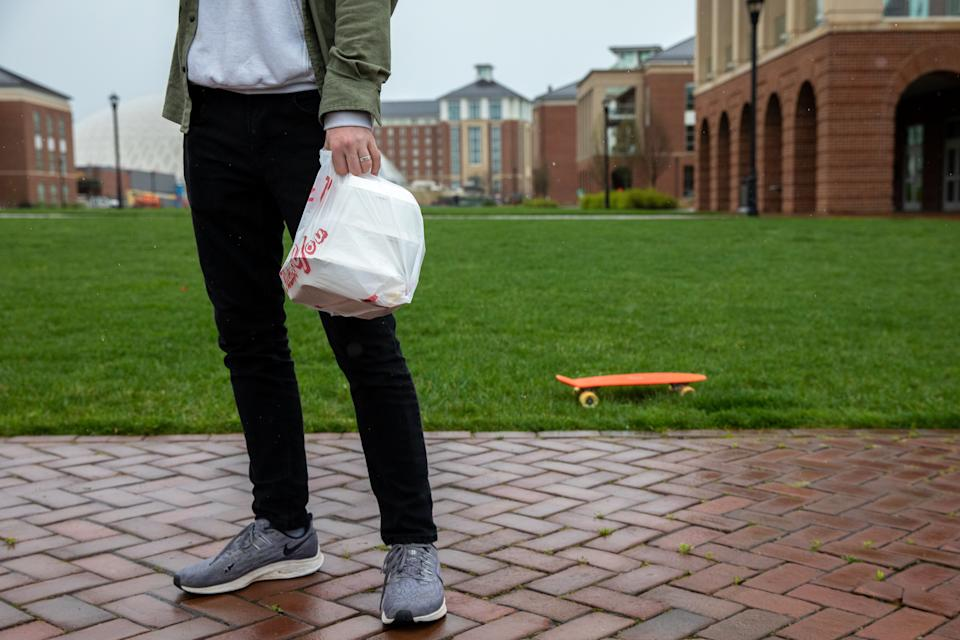 Ruben Erickson, a student at Liberty University in Lynchburg, Virginia, holds a bag of takeout food which he acquired from an on-campus dining hall on March 31, 2020. - Virginia's governor on March, 31, 2020 ordered all higher education institutions to halt any in-person instruction amid the coronavirus pandemic, a move likely directed at Liberty University, which initially declined to stop all on-campus teaching. (Photo by Amanda Andrade-Rhoades / AFP) (Photo by AMANDA ANDRADE-RHOADES/AFP via Getty Images)