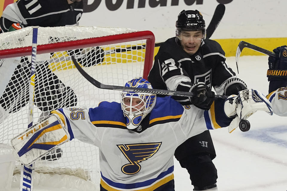 St. Louis Blues goaltender Ville Husso, bottom, stops a shot under Los Angeles Kings right wing Dustin Brown (23) during the first period of an NHL hockey game Friday, March 5, 2021, in Los Angeles. (AP Photo/Marcio Jose Sanchez)