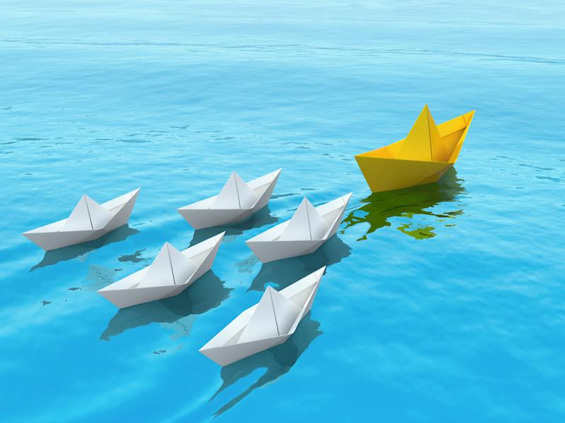 Paper ships sailing on a sea following the leader. Leadership concept 3d illustration.