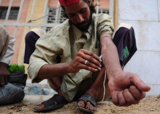 A Pakistani heroin addict self-injects on a street in Karachi. Some 27 million people worldwide are problem drug users, with almost one percent every year dying from narcotics abuse, while cannabis remains the most popular drug, a UN report showed Tuesday