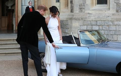 Prince Harry opens the door to the Jaguar allowing his wife to get into the passenger seat - Credit: Steve Parsons/PA