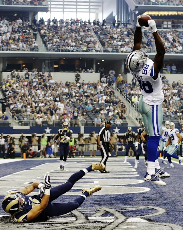 Dallas Cowboys wide receiver Dez Bryant (88) makes a touchdown reception as St. Louis Rams' Cortland Finnegan tumbles into the end zone during the first quarter of a NFL football game Sunday, Sept. 22, 2013, in Arlington, Texas. (AP Photo/LM Otero)