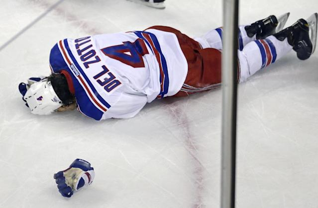 New York Rangers defenseman Michael Del Zotto (4) grabs his head after being hit by the puck during the first period in Game 1 of an NHL hockey playoffs Eastern Conference semifinal game against the Boston Bruins in Boston, Thursday, May 16, 2013. (AP Photo/Charles Krupa)