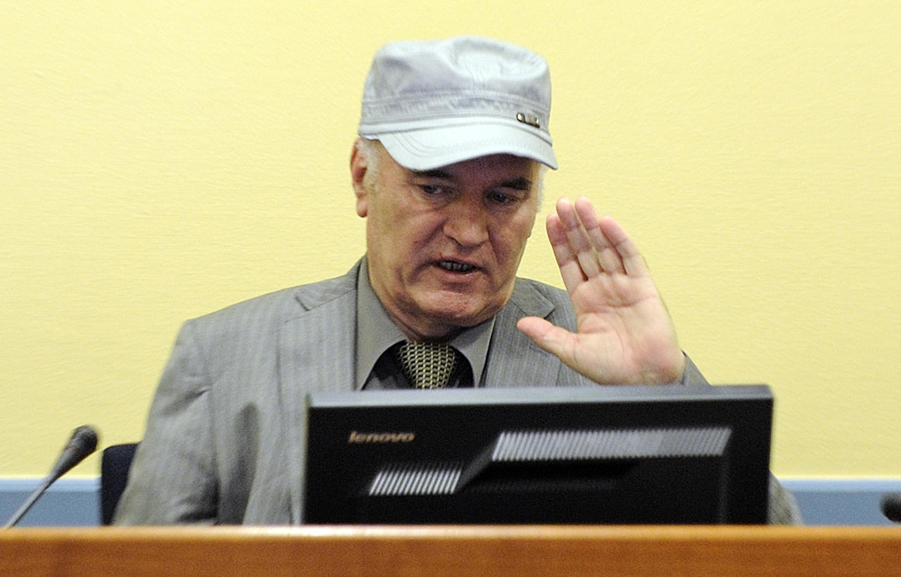 Former Bosnian Serb General Ratko Mladic salutes in the court room during his initial appearance at the U.N.'s Yugoslav war crimes tribunal in The Hague, Netherlands, Friday, June 3, 2011.Mladic's appearance Friday at the Yugoslav war crimes tribunal in The Hague is his first public appearance since he went into hiding nearly 16 years ago, when he was indicted for genocide and war crimes committed in the 1992-95 Bosnian war. (AP Photo/Martin Meissner, Pool)