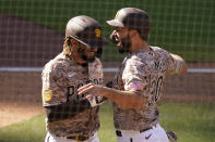 San Diego Padres' Eric Hosmer, right, reacts with teammate Fernando Tatis Jr after both scored off a two-RBI double by Tommy Pham during the eighth inning of a baseball game against the Los Angeles Dodgers, Sunday, April 18, 2021, in San Diego. (AP Photo/Gregory Bull)