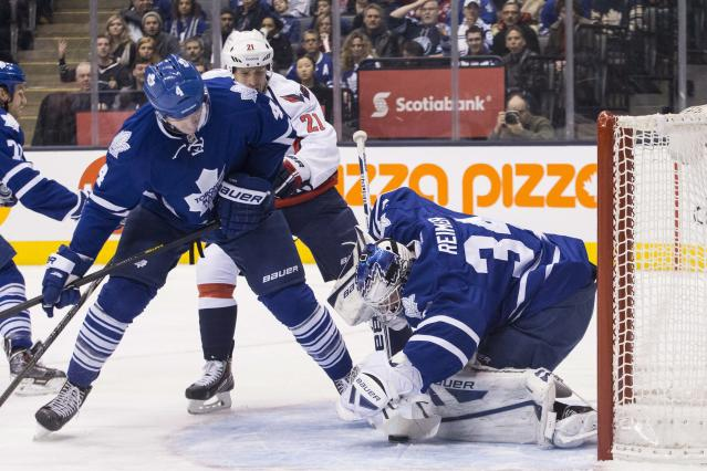 Toronto Maple Leafs goaltender James Reimer, right, makes a save as Washington Capitals center Brooks Laich, center, and Leafs defenseman Cody Franson close in during first period NHL hockey action in Toronto, on Saturday, Nov. 23 , 2013. (AP Photo/The Canadian Press, Chris Young)