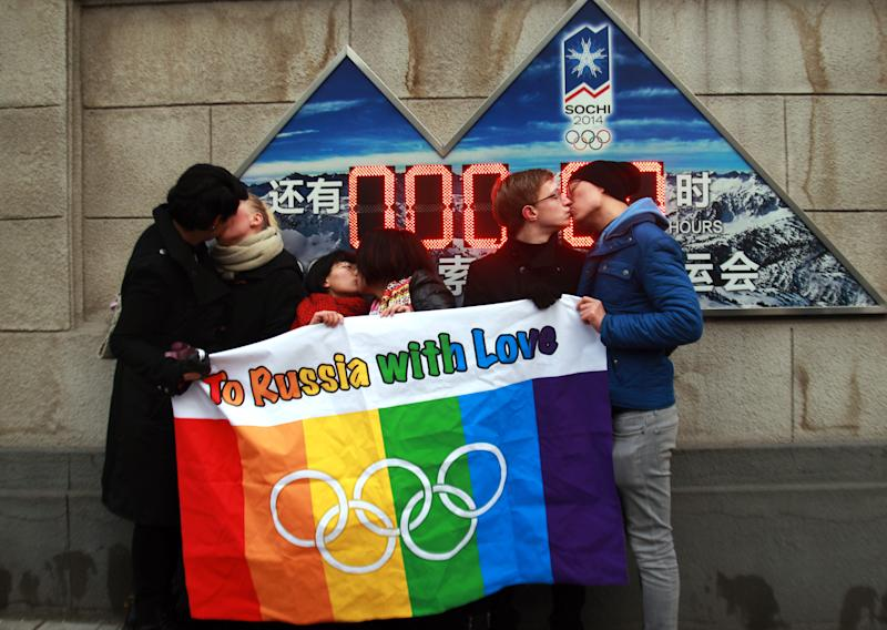 A group of gay and lesbian activists hold a banner of the rainbow flag, the Olympic rings and the words 'To Russia with love' as they stage a Valentine's Day kissing protest in Beijing onFeb.14, 2014. (STR via Getty Images)