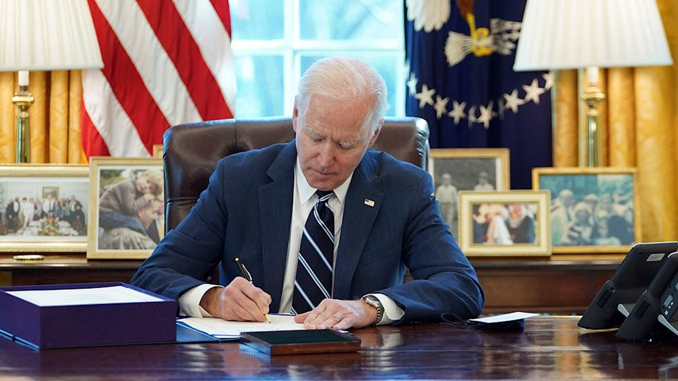 President Joe Biden signs the American Rescue Plan on March 11, 2021, in the Oval Office of the White House in Washington, DC. (Mandel Ngan/AFP via Getty Images)