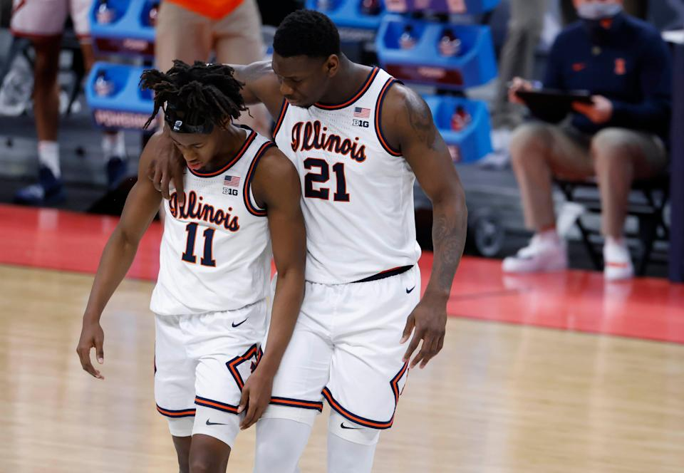 Illinois guard Ayo Dosunmu (11) is comforted by center Kofi Cockburn (21) during their second-round  to Loyola Chicago.