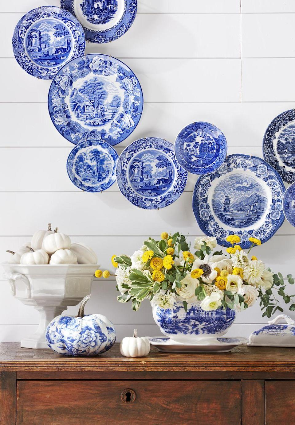 """<p>A vintage blue-and-white transferware tureen stuffed full of white and yellow flowers, with hints of greenery, looks great on buffet or as a Thanksgiving table centerpiece. Hang blue and white plates in a wreath shape on the wall and decoupage a white pumpkin with blue and white toile wallpaper (you can use color copies, too).</p><p><a class=""""link rapid-noclick-resp"""" href=""""https://www.amazon.com/Spode-Georgian-Plates-Assorted-Motifs/dp/B0000B2PK6/ref=sr_1_1?tag=syn-yahoo-20&ascsubtag=%5Bartid%7C10050.g.1371%5Bsrc%7Cyahoo-us"""" rel=""""nofollow noopener"""" target=""""_blank"""" data-ylk=""""slk:SHOP BLUE AND WHITE PLATES"""">SHOP BLUE AND WHITE PLATES</a></p>"""