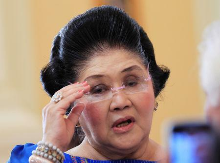 FILE PHOTO: Former Philippine first lady Imelda Marcos, who is now a congresswoman, adjusts her glasses after attending the first Mass of the newly built Santuario de San Ezekiel Moreno Catholic church in Las Pinas city, south of Manila, August 19, 2014. REUTERS/Romeo Ranoco/File Photo
