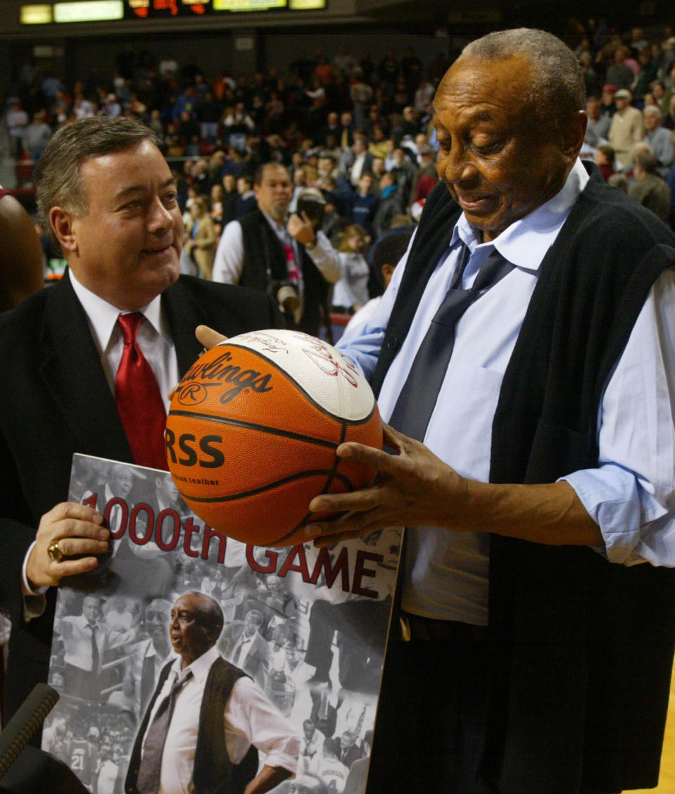 FILE - Temple head coach John Chaney, right, is presented with a ball by Temple athletic director Bill Bradshaw commemorating his 1000th game coached, in Philadelphia, in this Monday, Dec. 20, 2004, file photo. Temple beat Princeton 48-46. John Chaney, one of the nations leading Black coaches and a commanding figure during a Hall of Fame basketball career at Temple, has died. He was 89. His death was announced by the university Friday, Jan. 29, 2021. (AP Photo/Miles Kennedy, File)
