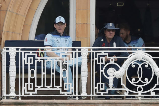 England captain Eoin Morgan, left, and England coach Trevor Bayliss sit on their team's balcony after Morgan was out for four runs during the Cricket World Cup match between England and Australia at Lord's cricket ground in London, Tuesday, June 25, 2019. (AP Photo/Matt Dunham)
