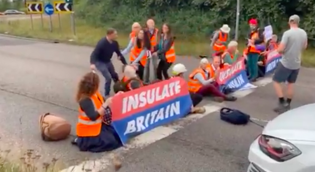 A motorist tried to drag an Insulate Britain protester off a roundabout at a junction of the M25. (LBC/Twitter)