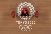 Li Fabin of China competes in the men's 61kg weightlifting event, at the 2020 Summer Olympics, Sunday, July 25, 2021, in Tokyo, Japan. (AP Photo/Luca Bruno)