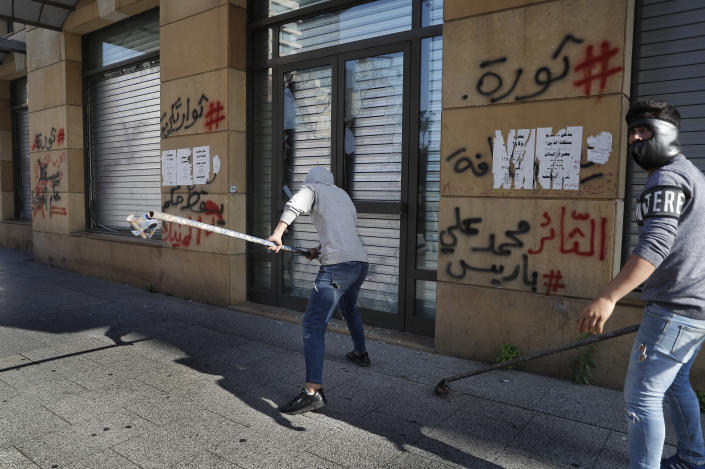 Anti-government protesters destroy bank windows during a protest against the deepening financial crisis, in Beirut, Lebanon, Tuesday, April 28, 2020. Hundreds of protesters in Lebanon's northern city of Tripoli set fire Tuesday to two banks and hurled stones at soldiers, who responded with tear gas and batons in renewed clashes triggered by an economic crisis spiraling out of control amid a weeks-long virus lockdown. (AP Photo/Hussein Malla)