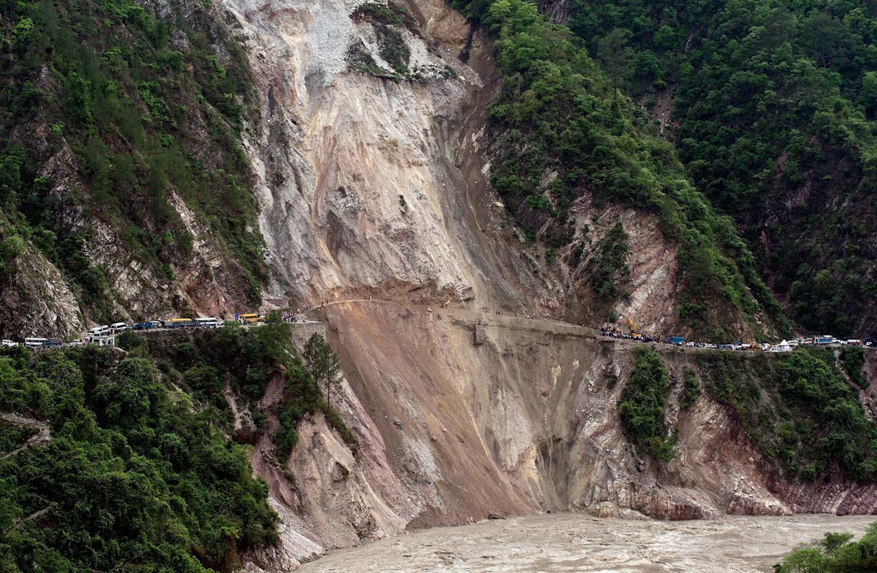 In this picture taken June 25, 2013, vehicles wait on the either side following a landslide due to heavy rains between Rudraprayag and Srinagar. Around 1,000 people have been killed in flash floods and landslides in northern India, as a top official warned June 24 that rebuilding of the devastated Himalayan region would take years.   AFP PHOTO/MANAN VATSYAYANA
