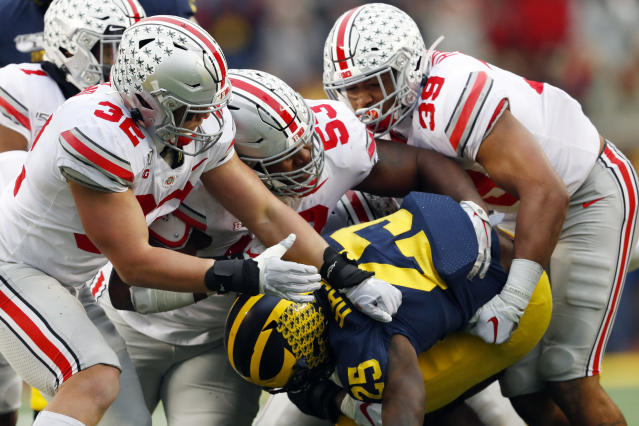 Ohio State linebackers Tuf Borland (32), Davon Hamilton (53) and Malik Harrison (39) smother Michigan running back Hassan Haskins (25) in the second half of an NCAA college football game in Ann Arbor, Mich., Saturday, Nov. 30, 2019. (AP Photo/Paul Sancya)
