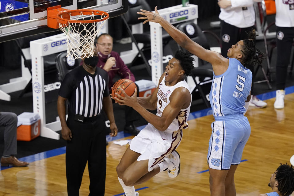 Florida State guard Scottie Barnes (4) drives to the basket at North Carolina forward Armando Bacot (5) defends during the second half of an NCAA college basketball game in the semifinal round of the Atlantic Coast Conference tournament in Greensboro, N.C., Friday, March 12, 2021. (AP Photo/Gerry Broome)