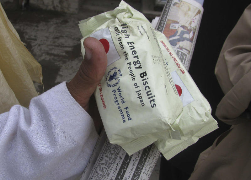 People buy high protein biscuits donated for flood victims, in Bannu, Pakistan on Wednesday, Oct. 13, 2010. (AP Photo/Ijaz Muhammad)
