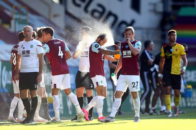 Burnley players cool off in the warm temperatures of Thursday's match (Michael Steele/NMC Pool/PA)