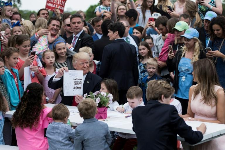 US President Donald Trump, Barron Trump (R) and First Lady Melania Trump join others to write notes to service members during the Easter Egg Roll on the South Lawn of the White House on April 17, 2017