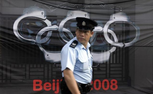 """A policeman walks past a banner from the France's press freedom activist group """"Reporters Sans Frontieres"""" (Reporters Without Borders) in front of the Beijing's liaison office in Hong Kong December 10, 2007."""